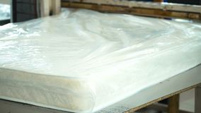 Plant for making Ready mattress is packed in transparent polyethylene and put markings. Employee of plant seals plastic on ready-to-sell goods for a stock video