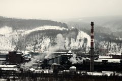 Plant of methanol and synthetic resins. Manufacturers among the mountains in winter royalty free stock photos