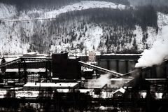 Plant of methanol and synthetic resins. Manufacturers among the mountains in winter royalty free stock images