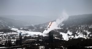 Plant of methanol and synthetic resins. Manufacturers among the mountains in winter. Flambeau light (candle) - controlled or emergency combustion of associated stock photography