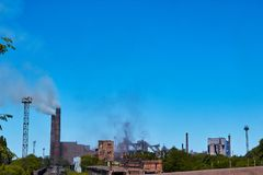 The plant pollutes the environment. Environmental pollution of nature plant. A factory with smoking pipes near the water. Emission. S of smoke into the stock photography