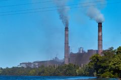 The plant pollutes the environment. Environmental pollution of nature plant. A factory with smoking pipes near the water. Emission. S of smoke into the royalty free stock photography