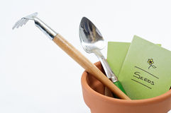 Plant Pot Tools and Seeds. Close up of a terracotta plant pot containing seed packet and potting tools Stock Photography