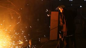 Plant for the production of steel. An electric melting furnace. Factory worker takes a sample for metal.  stock video footage