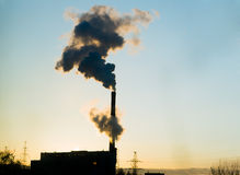 Plant smoke pollution. Smoking plant on the sunsetting background Royalty Free Stock Photography