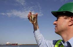 Plant specimen. An environmental engineer, wearing protective clothing, with a plant sample in a specimen jar, with a beautiful blue sky behind him and a ship stock image
