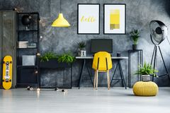 Home office with yellow skateboard. Plant in striped pot on braided pouf in yellow home office with skateboard and lamp royalty free stock image
