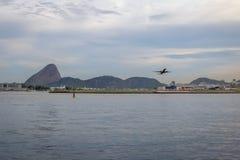 Plant ta av på Rio de Janeiro Airport med Sugar Loaf på bakgrund - Rio de Janeiro, Brasilien arkivfoton