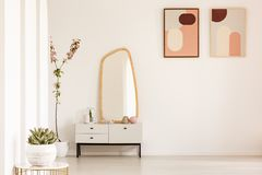 Plant on table and mirror on white cabinet in simple living room Stock Image