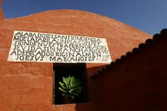 Plant wall. A wall of a red church with early Spanish or Quetiwan text and a bright green plant in the center Stock Photos