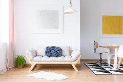 Multifunctional room with gallery. Plant and white fur near beige sofa with blue pillow in multifunctional room with gallery royalty free stock images
