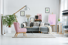 Designer`s lamp in living room. Plant in white pot and mirror in living room with vintage furnishings and designer`s lamp royalty free stock images