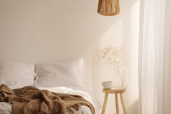 Plant on wooden stool next to bed with brown blanket in white simple bedroom interior royalty free stock images
