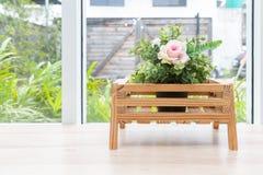Planta artificial en cesta en la tabla de madera con el backgroun del jardín imagen de archivo