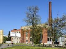 Planta con un tubo grande, central térmico en la ciudad imagenes de archivo