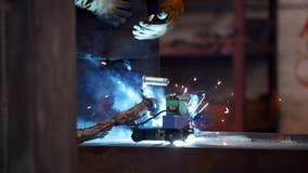 Planta de la construcción Un hombre en un casco usando una soldadora almacen de metraje de vídeo
