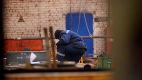 Planta de la construcción Un trabajador del hombre que se sienta cerca de la máquina de elevación metrajes