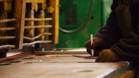 Planta de la construcción Un trabajador que hace marcas con un marcador blanco almacen de metraje de vídeo
