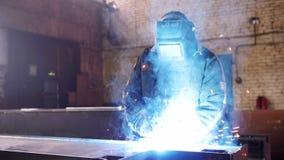 Planta de la construcci?n Un hombre que se sienta en su lugar de trabajo y que usa una soldadora Iluminaci?n azul brillante metrajes