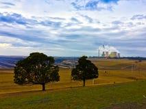 Planta de la electricidad de la energía del carbón que emite humo del gas al cielo azul nublado foto de archivo