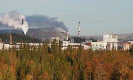 Planta de mina en Rusia, bosque otoñal, edificios de la fábrica, escoria Fotos de archivo libres de regalías