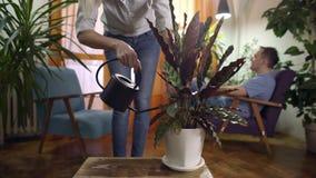 Planta de riego de la mujer joven en la lectura casera moderna del hombre de la tableta almacen de metraje de vídeo