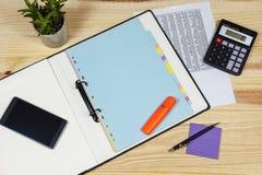 Planta en conserva en un escritorio de los contables con una calculadora Fotografía de archivo libre de regalías