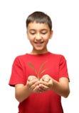 Planta feliz da terra arrendada do menino nas mãos Imagens de Stock Royalty Free