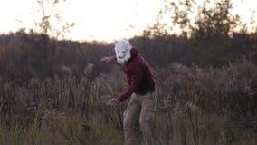 Planta geral No campo do outono, um indivíduo alto em uma máscara do urso dança 4K Mo lento filme