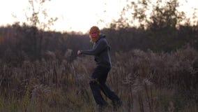 Planta geral No campo do outono uma dança do indivíduo em uma máscara de um macaco 4K Mo lento vídeos de arquivo