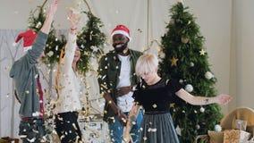 Planta geral nos jovens de dança de confetes diferentes dos flutches das raças as meninas e os meninos bonitos estão comemorando video estoque