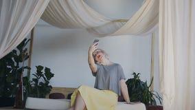 Planta geral Uma menina com cabelo branco senta-se na borda de uma cama bonita e pegara-se no telefone Mulher de Celphy na vídeos de arquivo