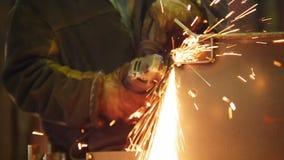 Planta industrial da construção Um homem que usa uma máquina de moedura Moendo o lado do detalhe Sparkles do fogo video estoque