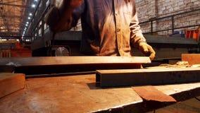 Planta industrial de la construcción Un hombre que sostiene una máquina de pulir y cortar alrededor el detalle por las marcas almacen de metraje de vídeo
