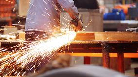 Planta industrial de la construcción Un hombre usando una máquina de pulir Pulido del detalle Chispas del fuego almacen de video