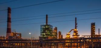 Planta industrial ou fábrica da refinaria de petróleo no por do sol, nos tanques da destilaria do armazenamento e no encanamento  imagens de stock royalty free
