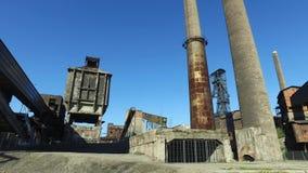 Planta metalúrgica abandonada vieja - instalación de coquefacción, chimeneas, torre de la mina de carbón metrajes