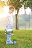 Planta molhando da criança asiática fora Fotos de Stock Royalty Free