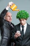 Planta molhando da pessoa na cabeça do homem de negócios Imagem de Stock