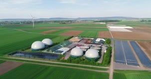 Planta para la producción de biogás en el campo verde, planta para la producción de biogás contra la perspectiva del viento almacen de metraje de vídeo