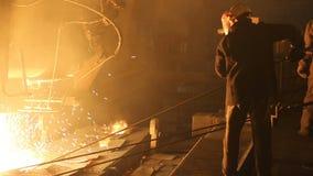Planta para la producci?n de acero Un horno fusorio eléctrico El obrero recoge una muestra para el metal almacen de metraje de vídeo