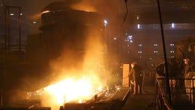 Planta para la producci?n de acero Un horno fusorio eléctrico El obrero recoge una muestra para el metal almacen de video