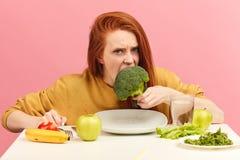 Plantaardig dieet De droevige saaie broccoli van de vrouwenholding op vork terwijl het maken van grimas royalty-vrije stock foto