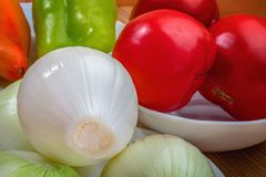 Plantaardig stilleven Gepelde uien, rode tomaten en paprika's royalty-vrije stock foto
