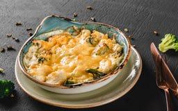 Plantaardige Frittata met aardappel, broccoli, kaas in plaat over donkere achtergrond Gezond veganistvoedsel, het schone eten stock afbeeldingen