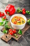 Plantaardige frittata met broccoli, rode groene paprika en rode ui in gietijzerkoekepan Mening van hierboven stock afbeeldingen