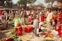Plantaardige markt in Indisch dorp met menigte van klanten die verse vruchten, tomaten en greens kopen stock foto's