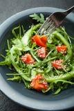 Plantaardige salade in een plaat, close-up Een vork houdt een rode tomaat royalty-vrije stock afbeeldingen