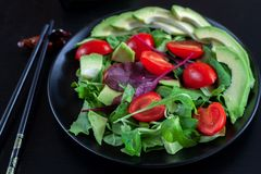 Plantaardige salade met avocado, kersentomaten, arugula en spinazie op een zwarte plaat op een donkere achtergrond royalty-vrije illustratie