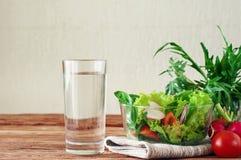 Plantaardige salade met een glas zuiver water stock fotografie